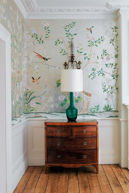 Wallpapered hallway with lamp on side table