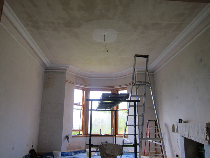 Room with large bay window being plastered